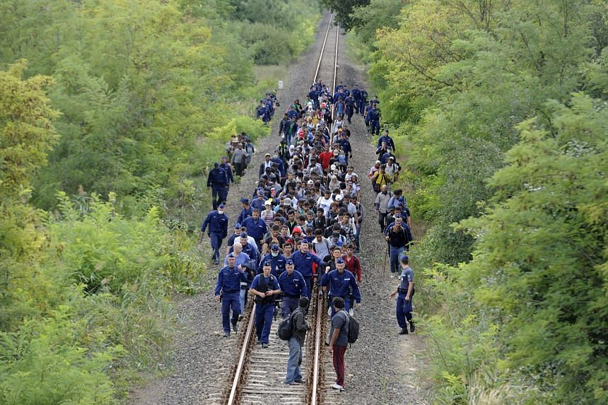 Migrants who left the police reception centre in Roszke in order to avoid being registered are escorted by police along the railway tracks connecting Horgos and Szeged, on Sept 8, 2015.