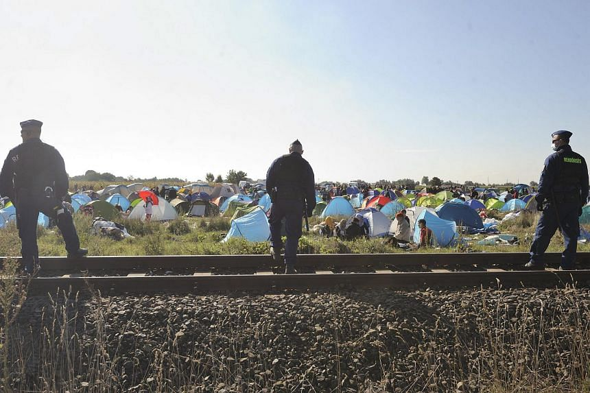Illegal migrants who arrived from Serbia are guarded by Hungarian police officers in the reception centre near the border village of Roszke, 180km south-east of Budapest, Hungary, on Sept 8, 2015.