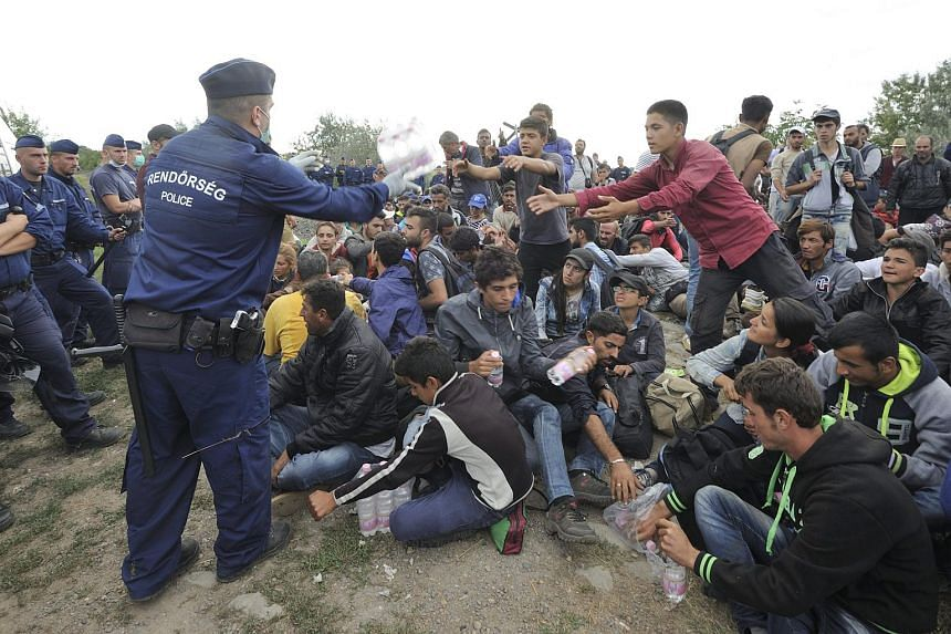Migrants who left the police reception centre in Roszke in order to avoid being registered are given water by the police near the railway tracks connecting Horgos and Szege on Sept 8, 2015.