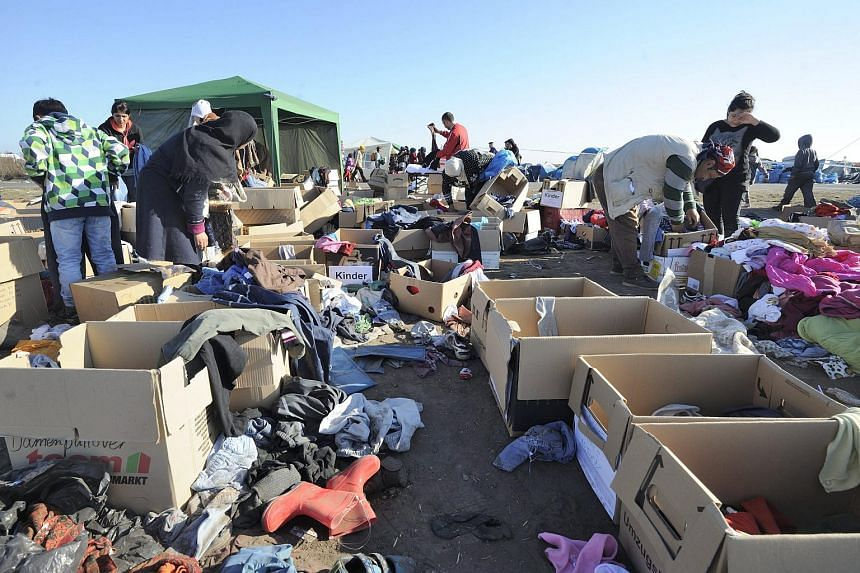 Illegal migrants who arrived from Serbia selecting items donated by charity organisations in the reception centre near the border village of Roszke, 180km south-east of Budapest, Hungary, on Sept 8, 2015.