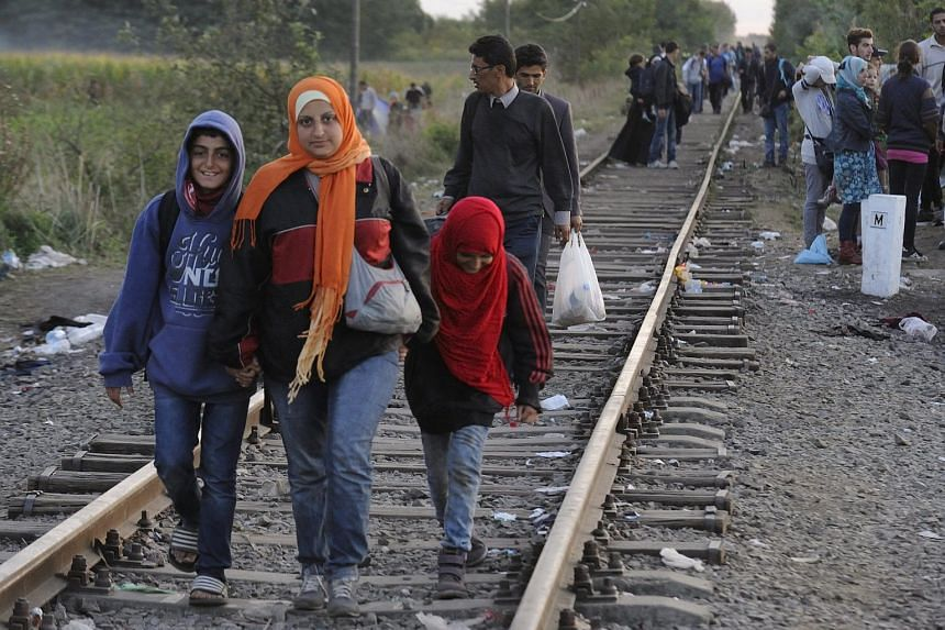 Migrants walking along the railway tracks connecting Horgos and Szeged in the vicinity of the Hungary-Serbian border near Roszke on Sept 8, 2015.