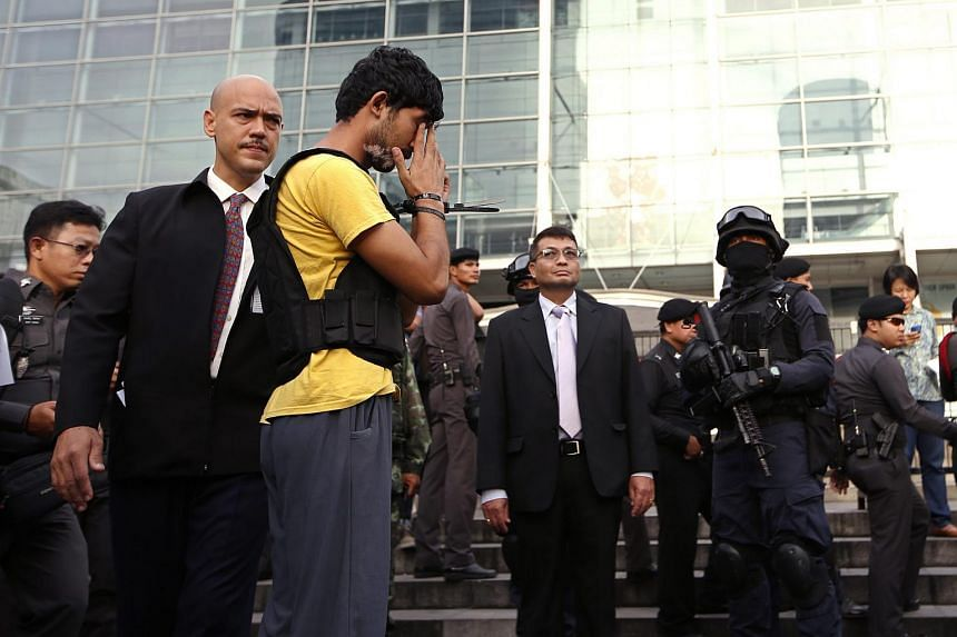 An Erawan Shrine bombing suspect, identified by Thai police as Yusufu Mieraili (in yellow), was taken to the scene for a reenactment of the crime on Sept 9, 2015.