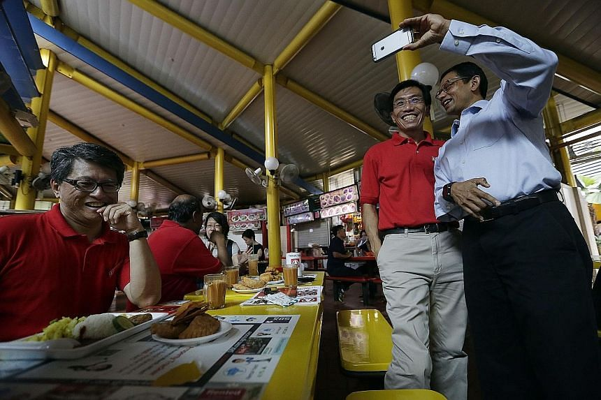 Dr Vivian Balakrishnan during a walkabout at Adam Road Food Centre on Sunday. A member of the public taking a selfie with Dr Chee Soon Juan at Adam Road Food Centre last Wednesday.