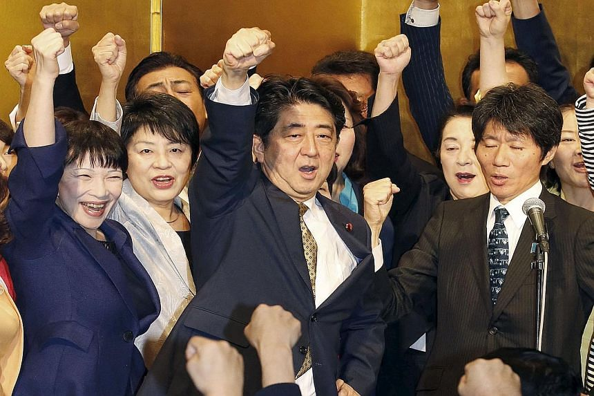 Japanese Prime Minister Shinzo Abe (centre) shouting slogans with fellow lawmakers during a kick-off ceremony in Tokyo yesterday for the party leadership polls, in which he was unopposed and won a rare second term.