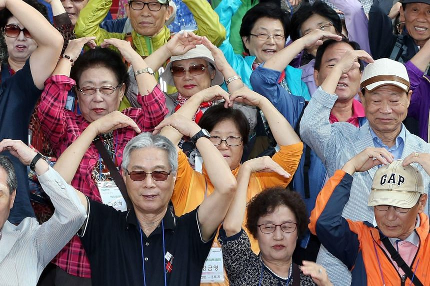 A group of South Koreans, separated from their kin in North Korea, making heart shapes at Seoul Station before they boarded a train bound for the South Korean border town of Cherwon yesterday. The excursion was co-organised by the Red Cross and the n
