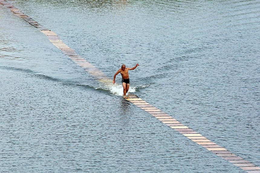 "A Shaolin monk breaking his own world record for ""running on water"" in Quanzhou, Fujian province. Shi Liliang from the Quanzhou Shaolin Temple managed to run 125m on 200 plywood planks laid across a reservoir, according to local media. It took three"