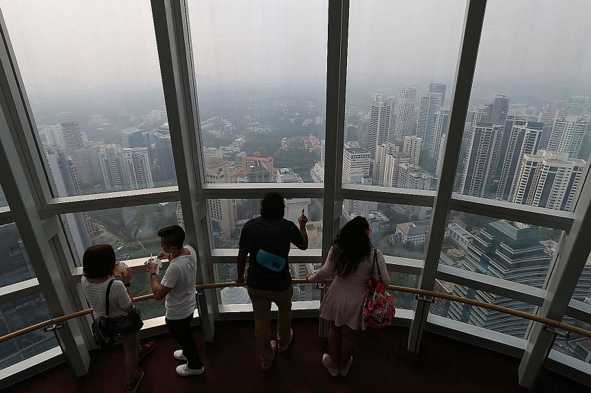 The Singapore skyline shrouded in haze at about 4.30pm yesterday, as seen from the Ion Sky observation deck. The hazy conditions are expected to persist due to smoke haze from Sumatra, says the NEA.
