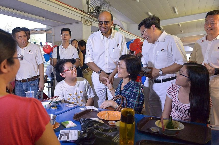 DPM Tharman Shanmugaratnam and PAP Aljunied GRC candidate Yeo Guat Kwang at Kovan Market and Food Centre yesterday.