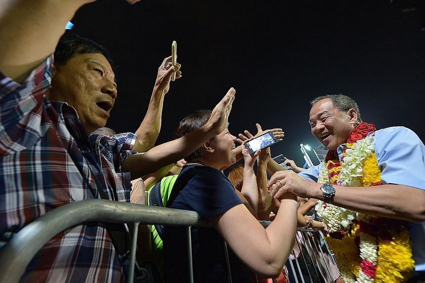 Workers' Party chief and Aljunied GRC candidate Low Thia Khiang greeting a supporter at the WP rally in Serangoon Stadium yesterday.