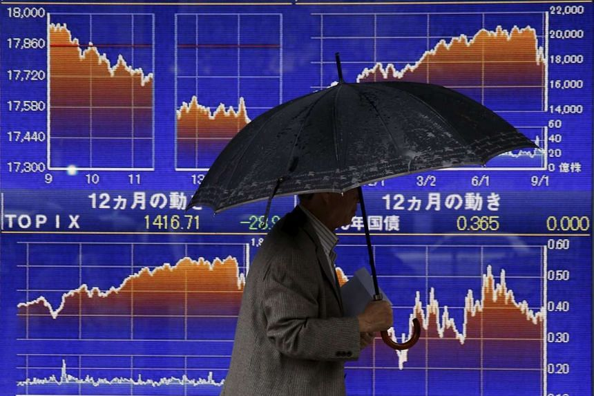A man walking past an electronic board displaying graphs showing recent movements of the Nikkei in Tokyo on Sept 8, 2015.