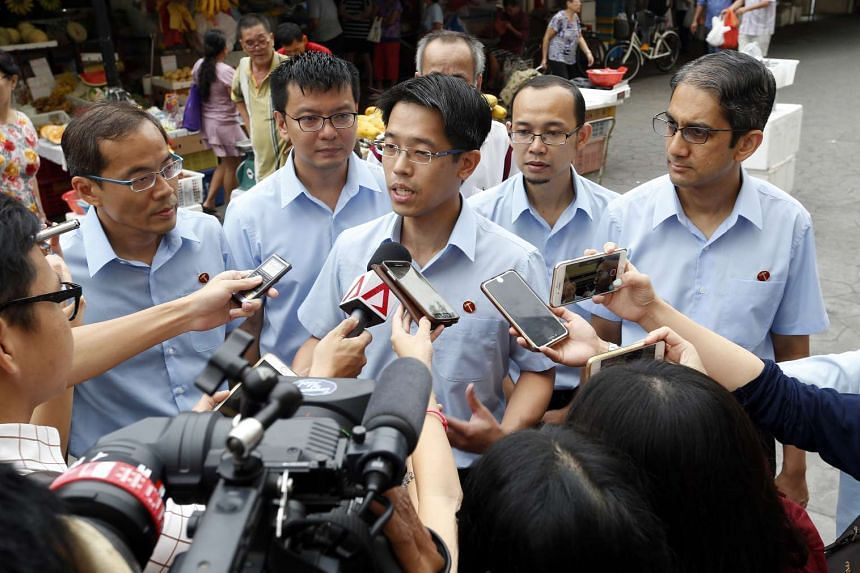 Workers' Party candidate Gerald Giam (centre) speaking with reporters during a walkabout at the Market and Food Centre at Block 58 New Upper Changi Road on Wednesday, Sept 9, 2015.