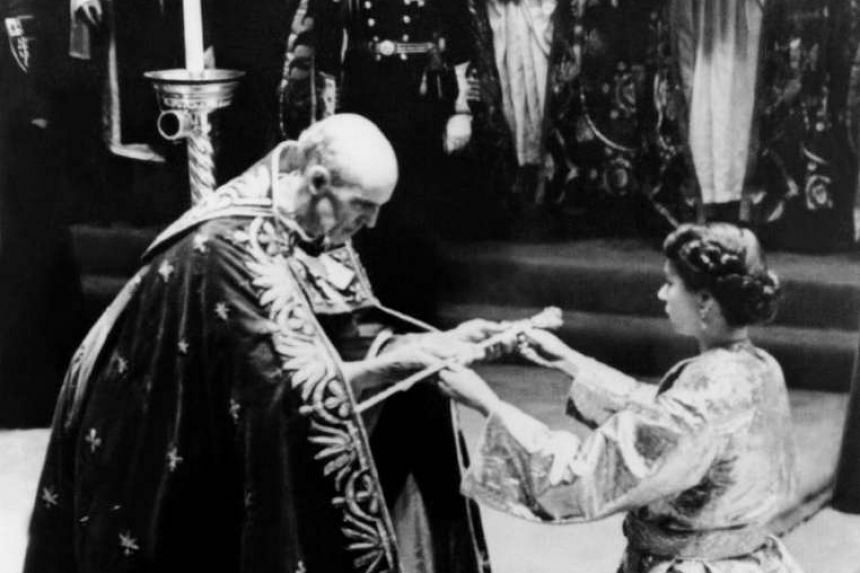 The Archbishop of Canterbury (left) giving Queen Elizabeth II a sword prior to her Coronation ceremony in Westminster Abbey.