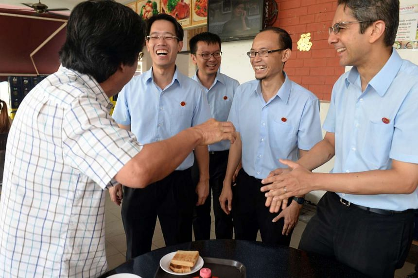 Workers' Party (WP) candidates for East Coast GRC (from left in blue) Gerald Giam, Daniel Goh, Mohamed Fairoz and Leon Perera greeting a resident during a walkabout in Simei on September 8, 2015.