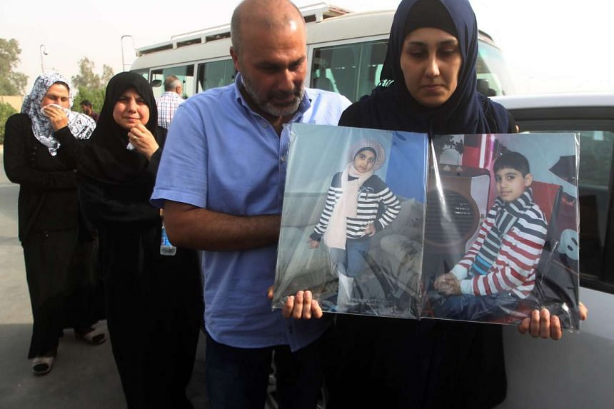 Zeinab Abbas holds portraits of her children following the arrival of their bodies in Baghdad for burial.