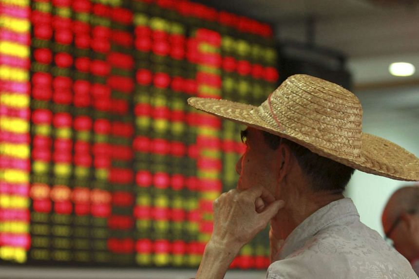 An investor looks at an electric board showing stock information at a brokerage house in Haikou, Hainan province, China, on Aug 11, 2015.