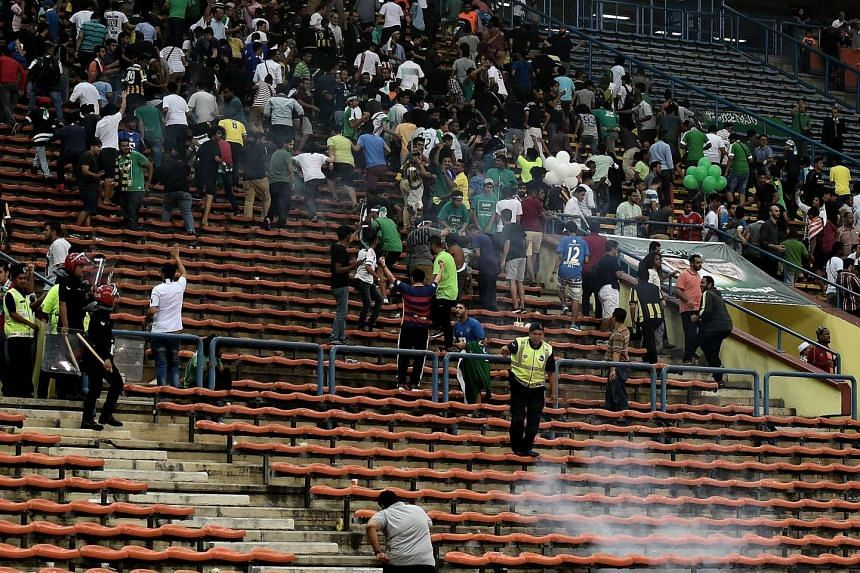 Malaysian police try to control the crowd after play was suspended during the 2018 FIFA World Cup qualifying football match between Malaysia and Saudi Arabia on Sept 8, 2015.