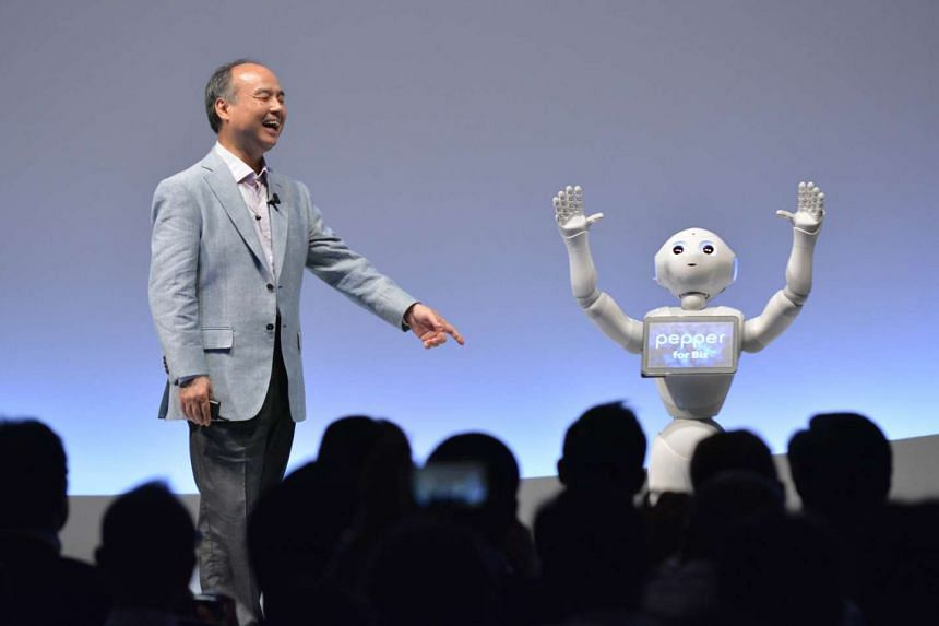 SoftBank Group representative Masayoshi Son and humanoid robot Pepper deliver a presentation at the SoftBank World 2015 in Tokyo on July 30, 2015.