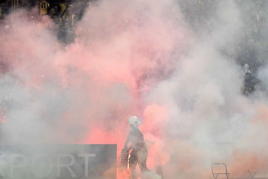 A Malaysian fireman douses flares thrown on the pitch during Tuesday night's 2018 World Cup qualifying football match.