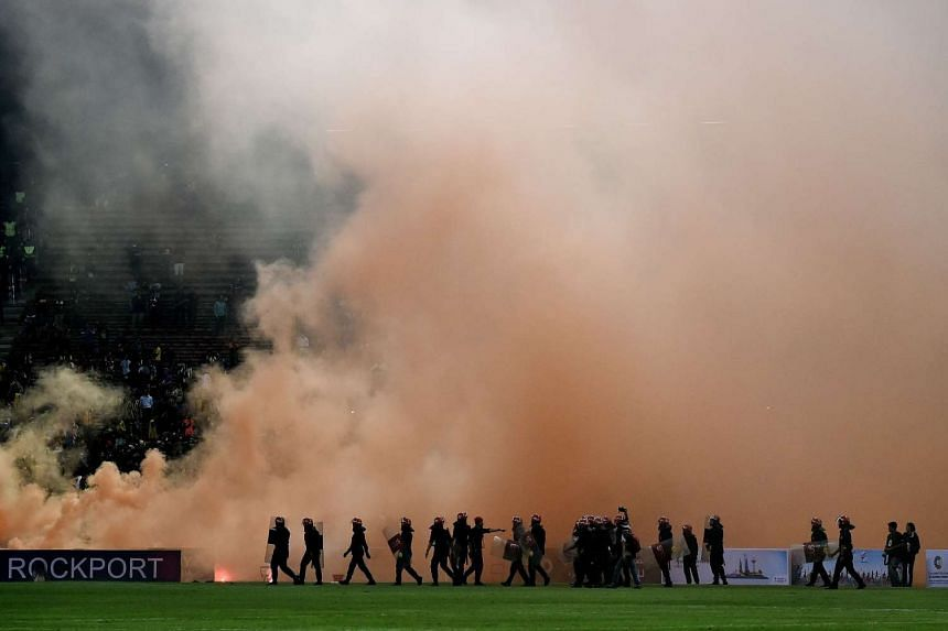 Malaysian riot police stand guard after flares were thrown on the pitch during Tuesday night's World Cup qualifying football match.
