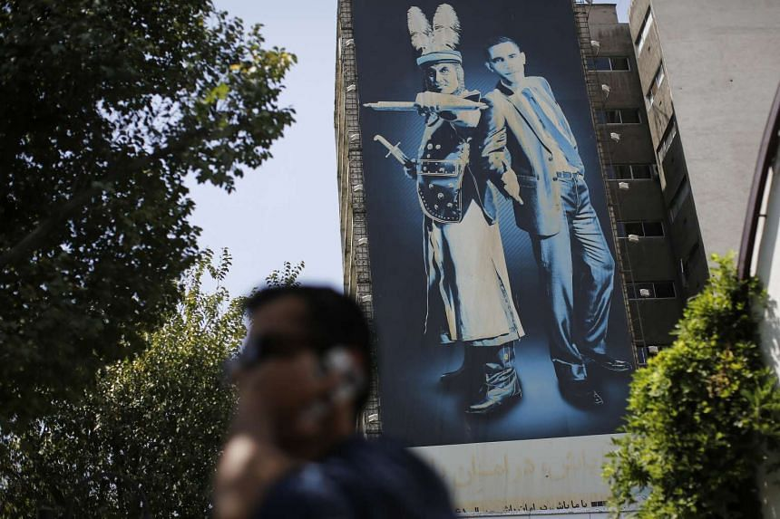 A mural depicting US President Obama standing beside an ancient Persian warrior sits on the wall of a building in Teheran on Aug. 24, 2015.