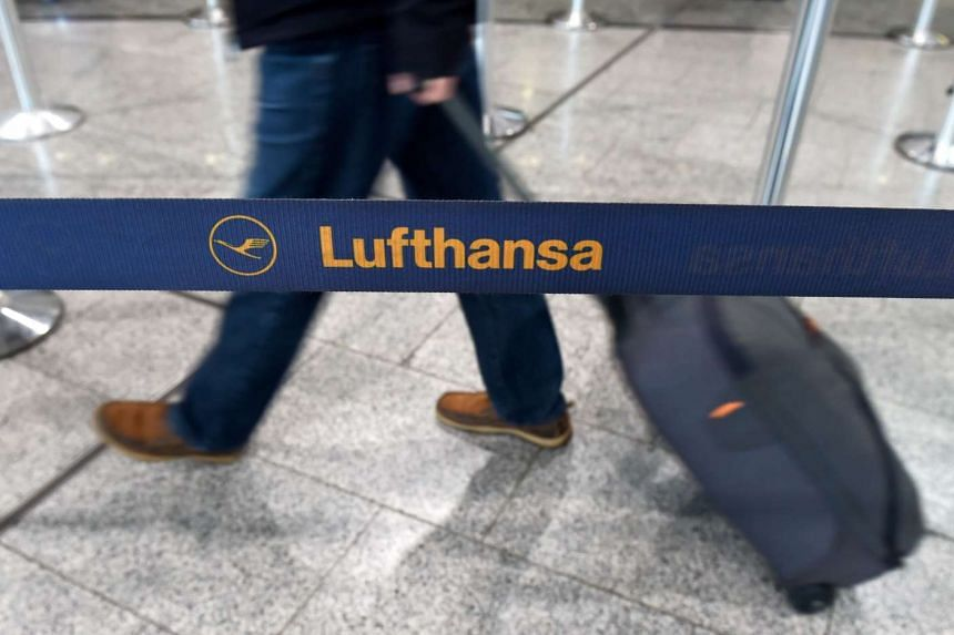 A person passes by a barrier ribbon with the logo of German airline Lufthansa at the airport in Frankfurt am Main, western Germany, as pilots of are on strike,