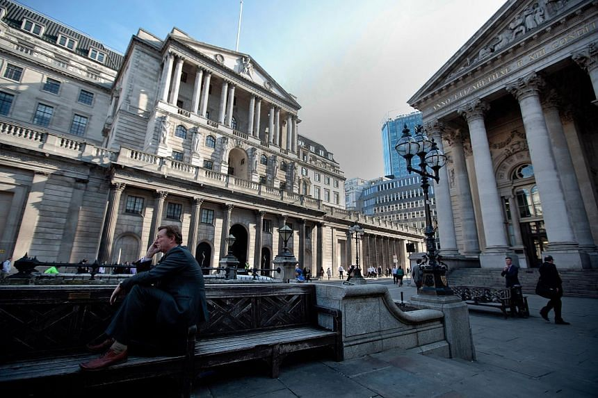 A businessman speaks on a mobile phone while sitting on a street bench outside the Royal Exchange (right), and Bank of England (left), in London.