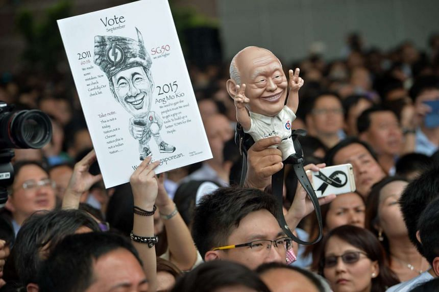 Supporters holding up a drawing of PM Lee Hsien Loong and a figurine of founding prime minister Lee Kuan Yew at the PAP's lunchtime rally outside UOB Plaza yesterday.