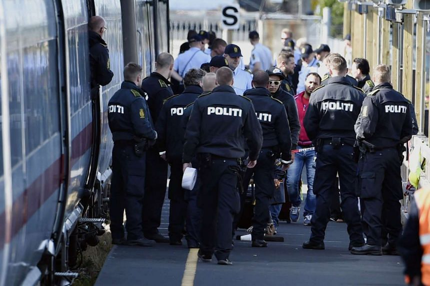 Danish police guard a train with migrants, mainly from Syria and Iraq, at Rodby railway station, southern Denmark.