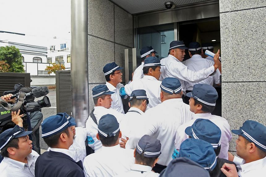 Police officers raiding the headquarters of the yakuza crime syndicate, the Yamaken-gumi, in Kobe, Hyogo prefecture, in western Japan on Sept 9, 2015.