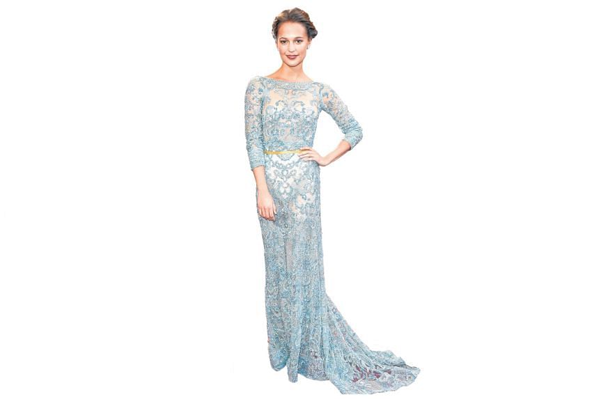 Looking every bit the red carpet darling in a lacy gown by Elie Saab. The high neckline is modest and demure, but she shows a bit of skin with an exposed back.