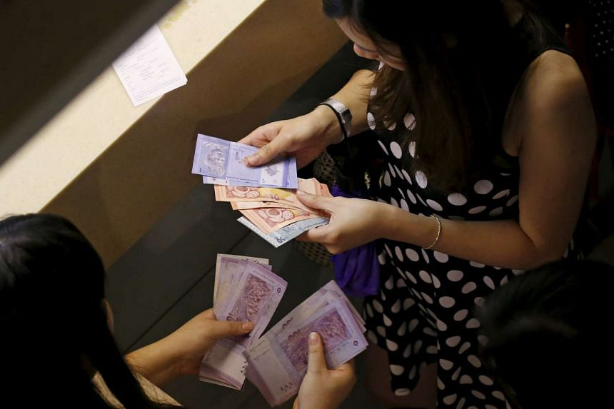 Customers count their ringgit notes outside a money changer at the central business district in Singapore on Aug 25, 2015.
