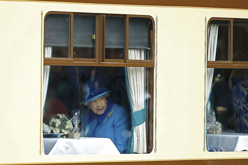 Queen Elizabeth II on board a steam train at Edinburgh Waverley Station in Scotland yesterday. The monarch ascended the throne at the age of 25 when her father, King George VI, died on Feb 6, 1952.