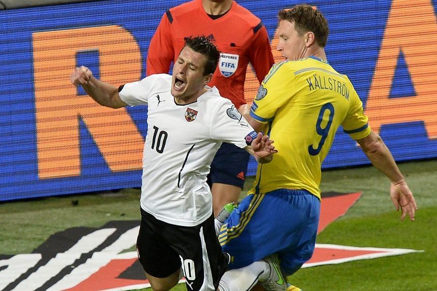 Austria's Zlatko Junuzovic (left) earns a penalty after he is fouled by Sweden's Kim Kallstrom during their Euro 2016 Group G qualifier. Austria won the game, played in Stockholm on Tuesday, 4-1.