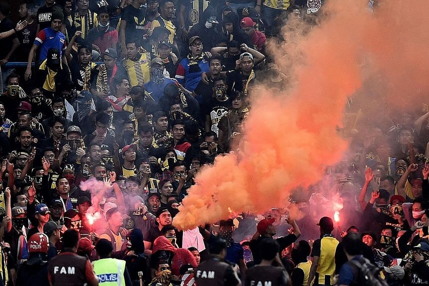 """Malaysian football fans burning flares in the stands during Tuesday's World Cup qualifier against Saudi Arabia. Flares thrown onto the pitch caused the game to be abandoned, with the Asian Football Confederation saying it is """"extremely disappointed""""."""