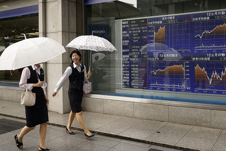 A stock market board in Tokyo, where shares soared 7.7 per cent yesterday. Stocks also rose in other Asian markets, including in Singapore where the STI gained 1.5 per cent.