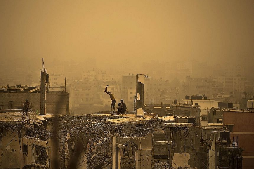 Palestinian workers in Gaza City removing debris from a building, one of many which were destroyed during the 50-day war between Israel and Hamas militants last year, amid a sandstorm on Tuesday.