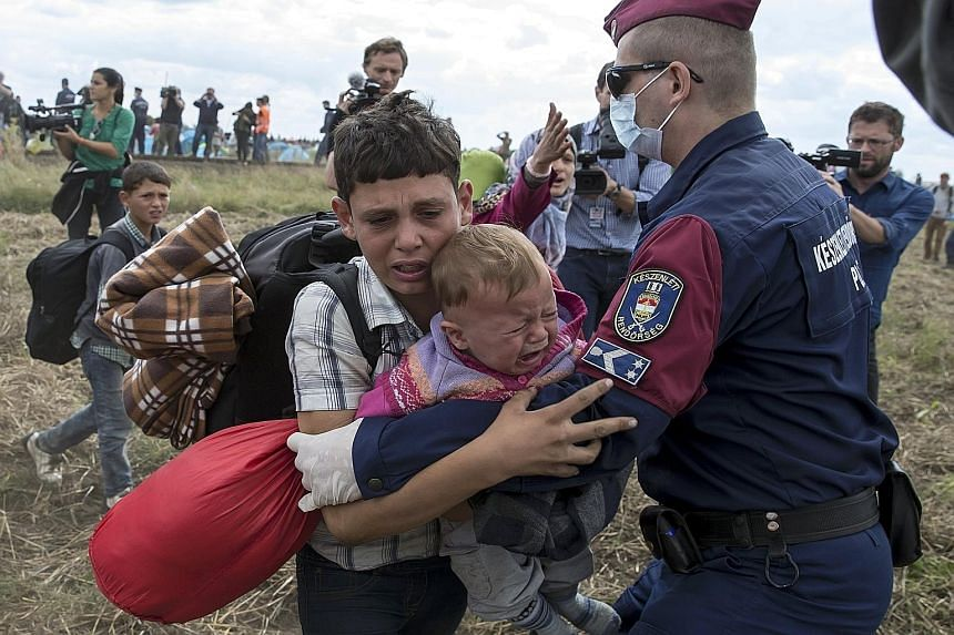 A Hungarian policeman attempting to stop a migrant child carrying a baby from running away from a collection point in Roszke, Hungary, on Tuesday. At least 400 desperate migrants have broken through police lines at the flashpoint town. Migrants yeste