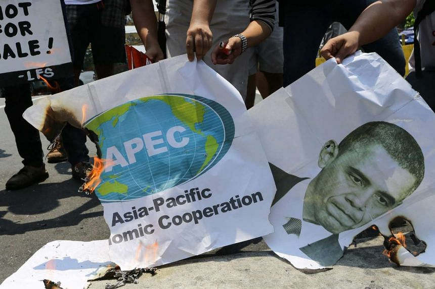 Filipino activists burn banners against the Asia-Pacific Economic Cooperation (APEC) and an image of US President Barack Obama (R) during a protest rally near the Malacanang presidential palace in Manila on September 7. PHOTO: EPA