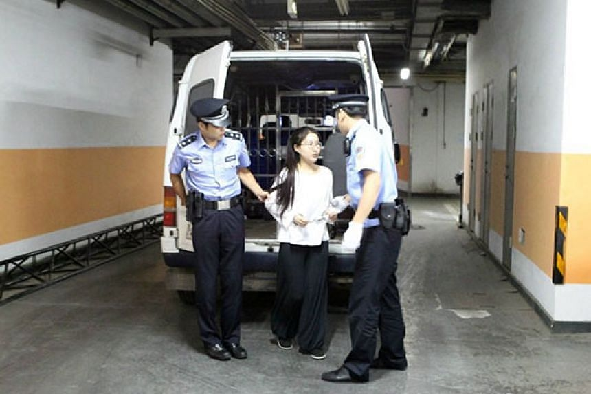 Guo Meimei (centre) gets off police car to stand trial at Beijing Dongcheng District People's Court on Thursday, Sept 10, 2015.