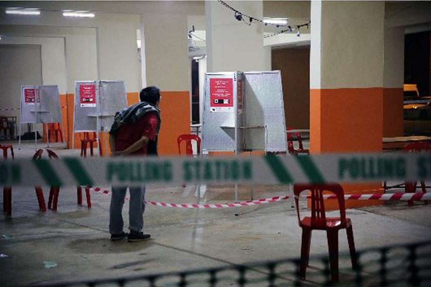 A curious bystander peeks at a polling booth on Sept 10, 2015, which has been set up for voting procedures the next day, on Sept 11.