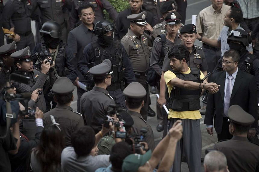 A foreign suspect in the Aug 17 Bangkok bombing, identified as Yusufu Mieraili (in yellow), is seen during a re-enactment with police officers near the Erawan shrine (not pictured) in Bangkok on Sept 9, 2015.