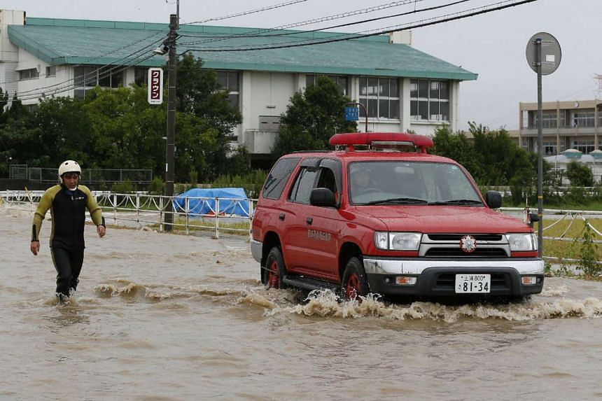 A firefighter walks alongside an emergency vehicle on a flooded street following heavy rains in Joso City, Ibaraki prefecture on Sept 10, 2015.