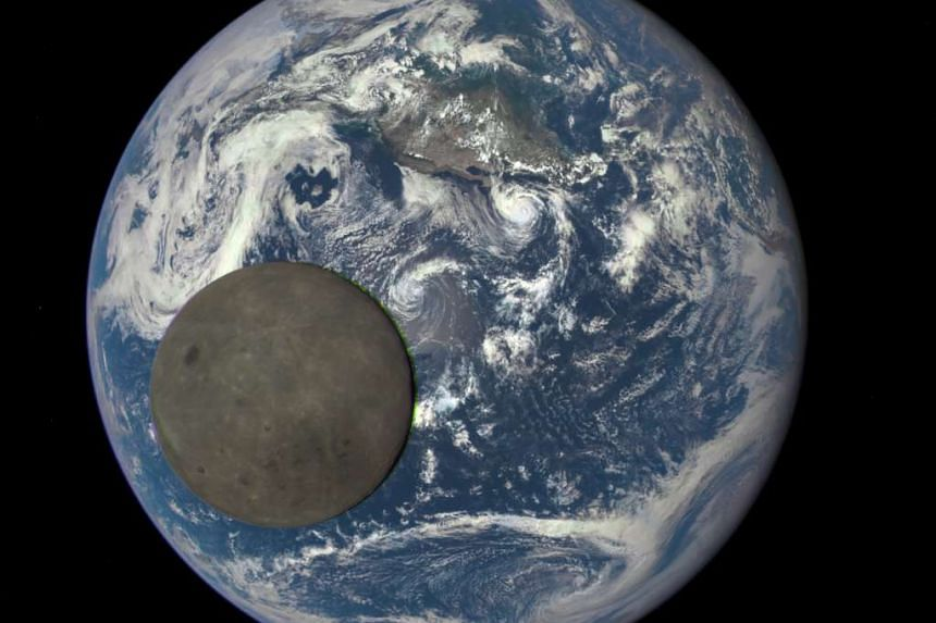 The far side of the moon, illuminated by the sun as it crosses between the DSCOVR spacecraft's Earth Polychromatic Imaging Camera (EPIC) camera and telescope, and the Earth is seen in a NASA image taken on July 16, 2015.