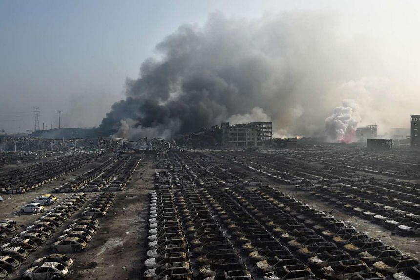 Smoke billowing behind rows of burnt out cars the morning after a series of explosions hit the city of Tianjin on Aug 13, 2015.