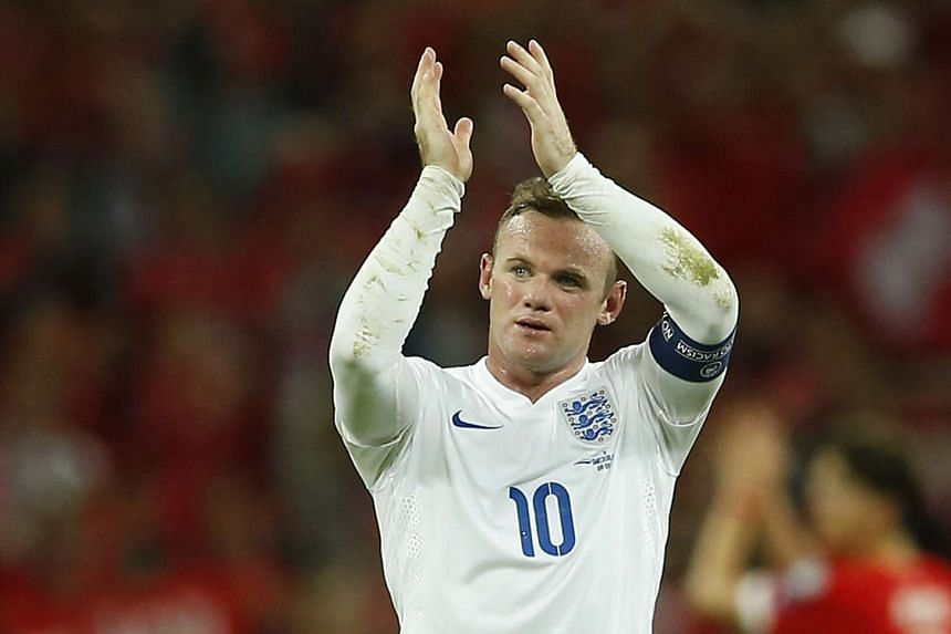 England's Wayne Rooney applauds the fans at the end of their 2-0 win over Switzerland.