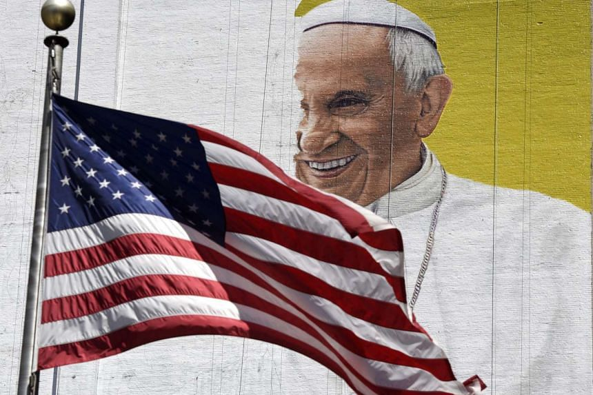 A US flag flies in front of an unfinished mural of Pope Francis in New York.