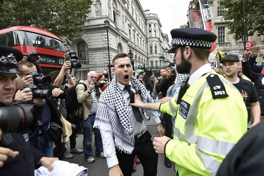 A demonstrator argues with police during a protest outside Downing Street.