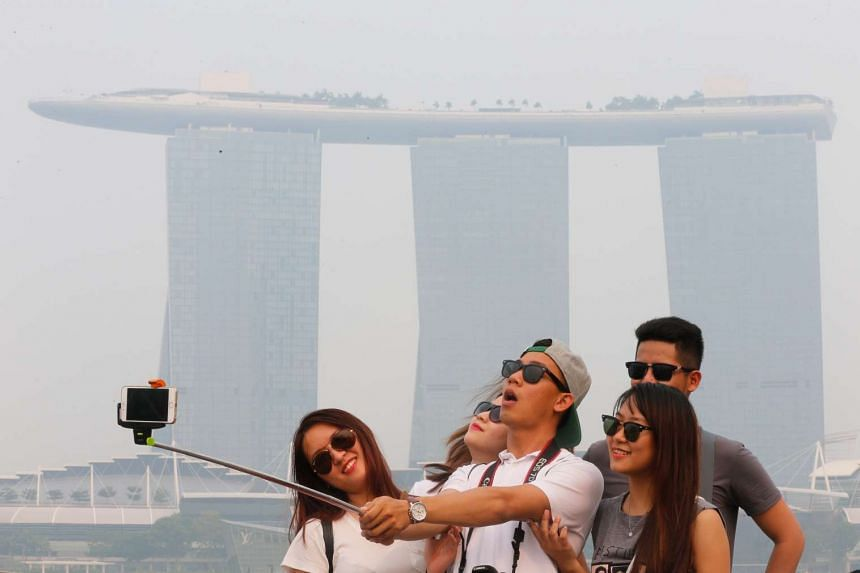 A group of tourists strike a pose at the Merlion Park at around 6pm on Sept 10, 2015.