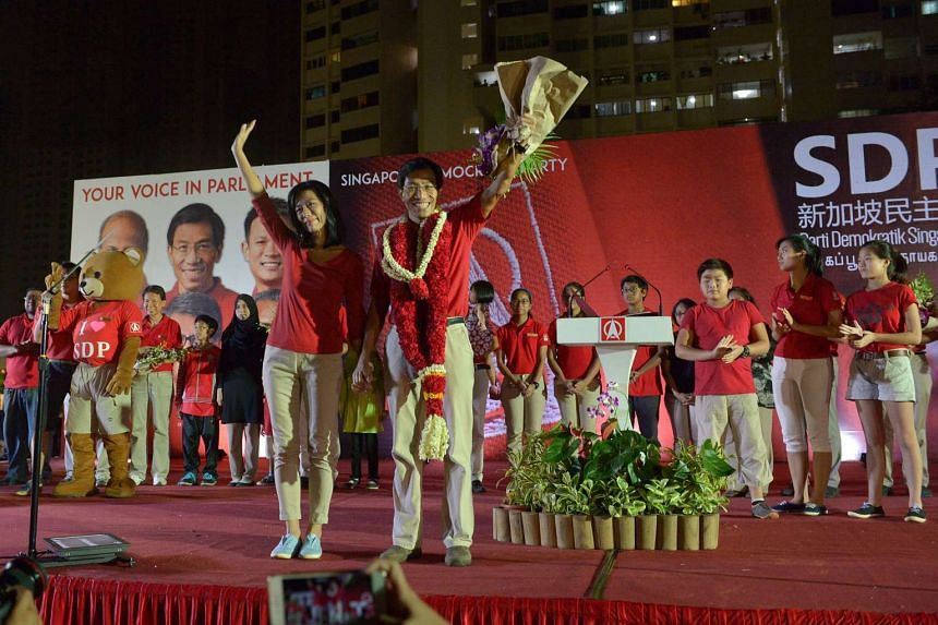 "SDP chief Chee Soon Juan and his wife Huang Chih-mei waving to the crowd after the party's rally in Clementi Avenue 6. Dr Chee urged voters to send him to Parliament to ""make the ministers work harder for you""."