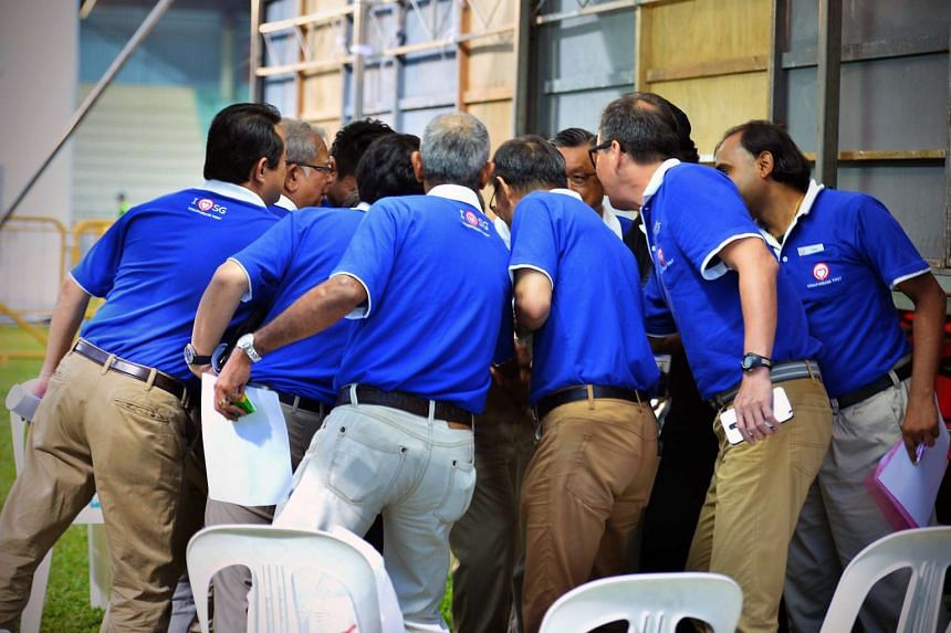 """SingFirst candidates huddling before the start of their rally for Tanjong Pagar GRC at Queenstown Stadium. They continued to attack the """"liberal immigration policies"""" of the ruling party and asked voters to judge the PAP on the last 10 years, and"""